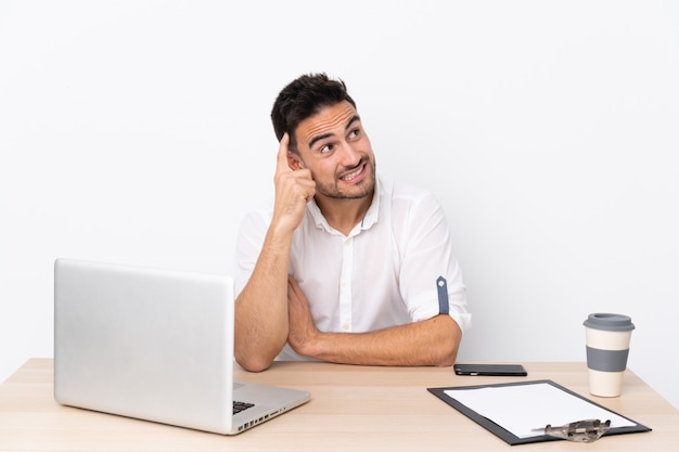 Uomo d'affari giovane con un telefono cellulare in un posto di lavoro che ha dubbi e con espressione del viso confuso