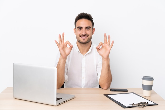Uomo d'affari giovane con un telefono cellulare in un posto di lavoro che mostra un segno ok con le dita