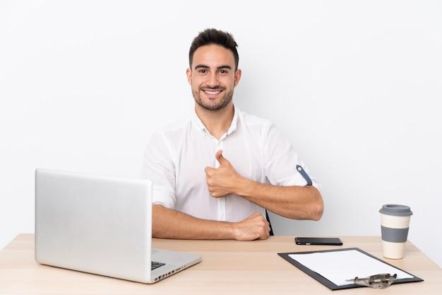Uomo d'affari giovane con un telefono cellulare in un posto di lavoro dando un pollice in alto gesto