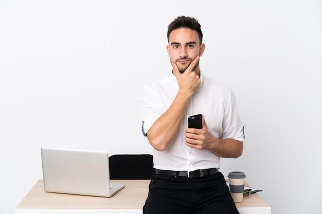 Uomo d'affari giovane con un telefono cellulare in un posto di lavoro pensando un'idea
