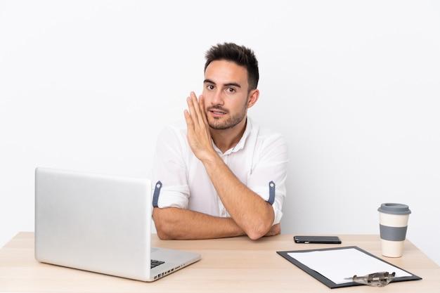 Uomo d'affari giovane con un telefono cellulare in un posto di lavoro sussurrando qualcosa