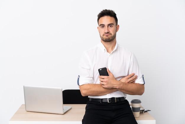 Uomo d'affari giovane con un telefono cellulare in un posto di lavoro triste