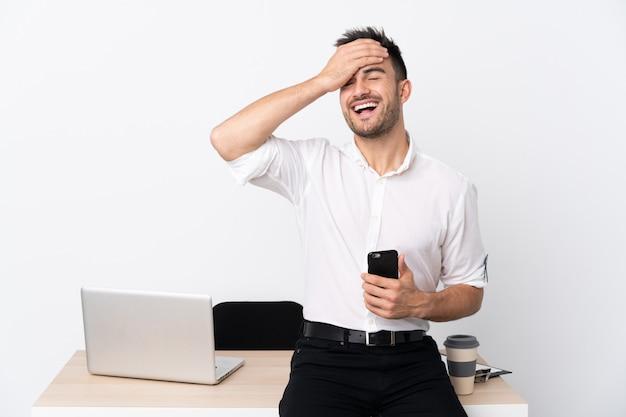 Uomo d'affari giovane con un telefono cellulare in una risata sul posto di lavoro