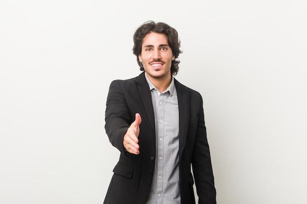 Uomo d'affari giovane contro un muro bianco allungando la mano nel gesto di saluto.
