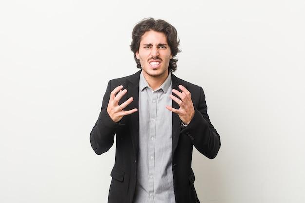 Uomo d'affari giovane contro uno sfondo bianco sconvolto urlando con le mani tese.