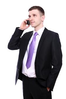 Uomo d'affari giovane e bello che per mezzo del cellulare