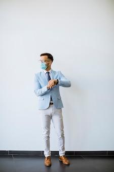 Uomo d'affari giovane ed elegante con maschera facciale si trova vicino al muro in ufficio e controlla il tempo sull'orologio