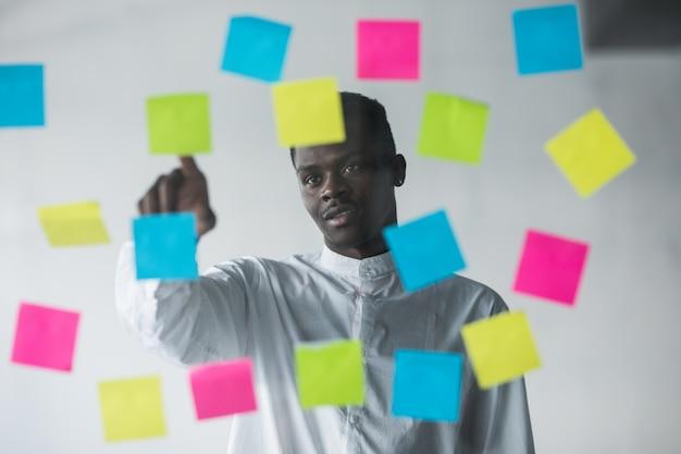 Uomo d'affari giovane in piedi davanti alla parete di vetro adesivi e appuntito scegliere il giusto adesivo al suo posto di ufficio