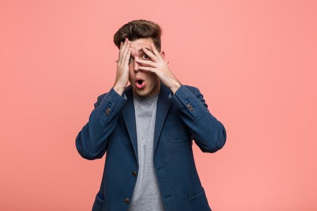 Uomo d'affari giovane naturale lampeggia attraverso le dita spaventato e nervoso.