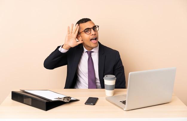 Uomo d'affari giovane nel suo ufficio con un computer portatile e altri documenti ascoltando qualcosa mettendo la mano sull'orecchio