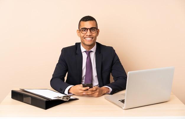 Uomo d'affari giovane nel suo ufficio con un computer portatile e altri documenti che inviano un messaggio con il cellulare