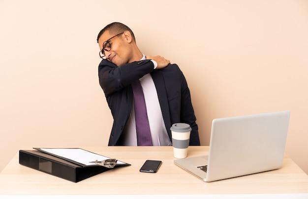 Uomo d'affari giovane nel suo ufficio con un computer portatile e altri documenti che soffrono di dolore alla spalla per aver fatto uno sforzo
