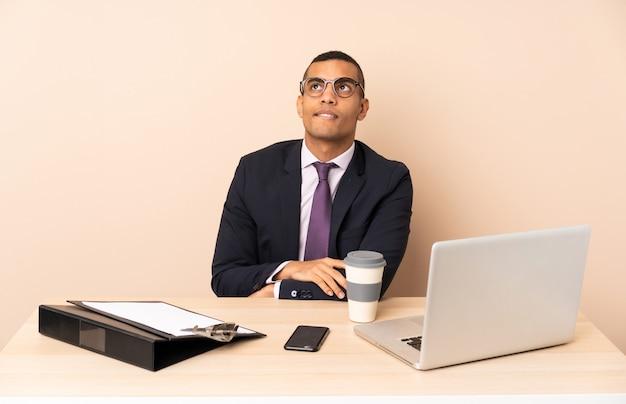 Uomo d'affari giovane nel suo ufficio con un computer portatile e altri documenti con espressione del viso confuso