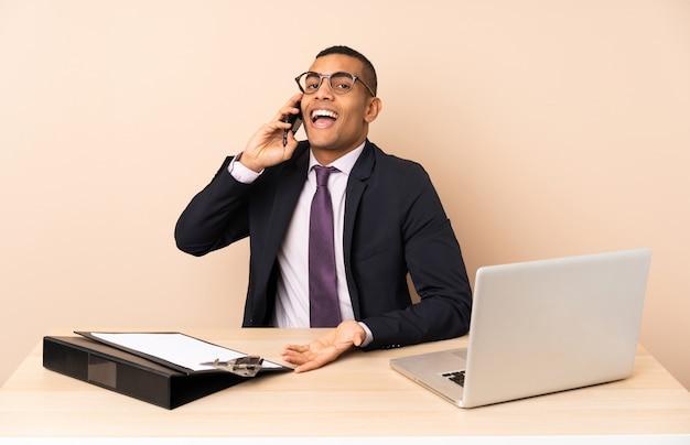 Uomo d'affari giovane nel suo ufficio con un computer portatile e altri documenti mantenendo una conversazione con il telefono cellulare con qualcuno