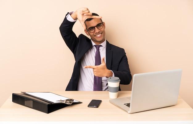 Uomo d'affari giovane nel suo ufficio con un computer portatile e altri documenti messa a fuoco faccia. simbolo di inquadratura