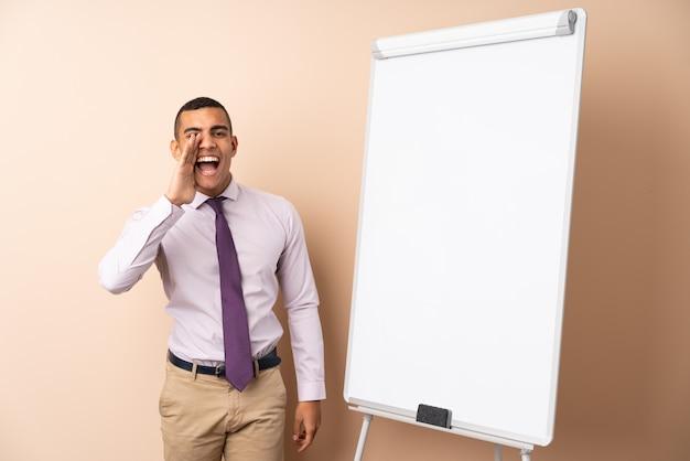 Uomo d'affari giovane sul muro isolato dando una presentazione sul bordo bianco e gridando con la bocca spalancata