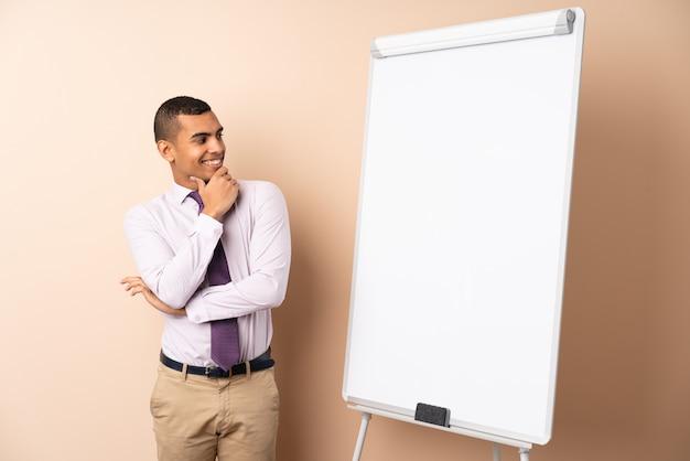 Uomo d'affari giovane sul muro isolato dando una presentazione sul bordo bianco e guardando lato