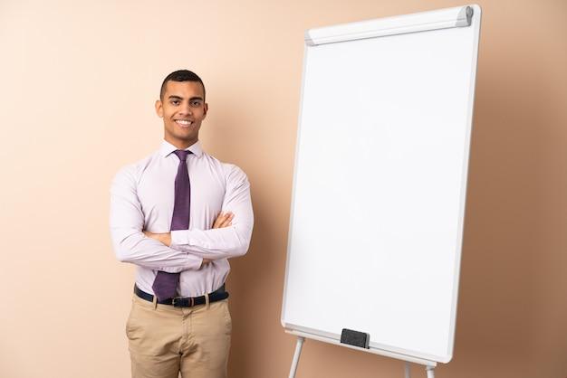 Uomo d'affari giovane sul muro isolato dando una presentazione sul bordo bianco e sorridente