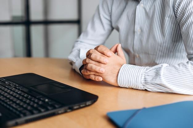 Uomo d'affari giunte mani sulla scrivania, lavorando sul computer