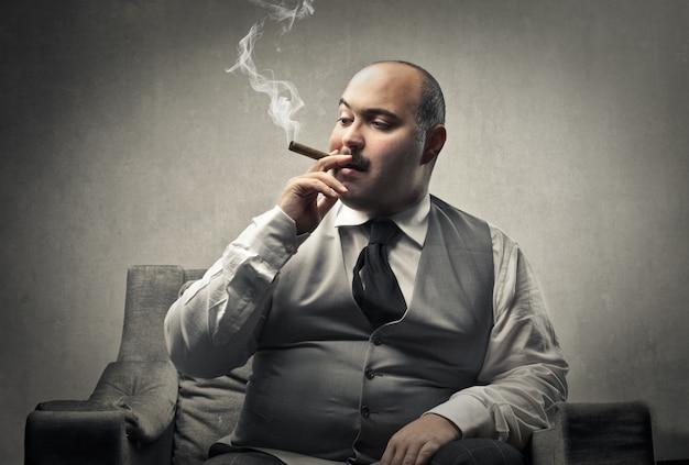Uomo d'affari grasso che fuma un sigaro