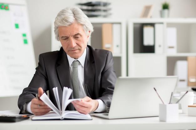 Uomo d'affari guardando attraverso le note