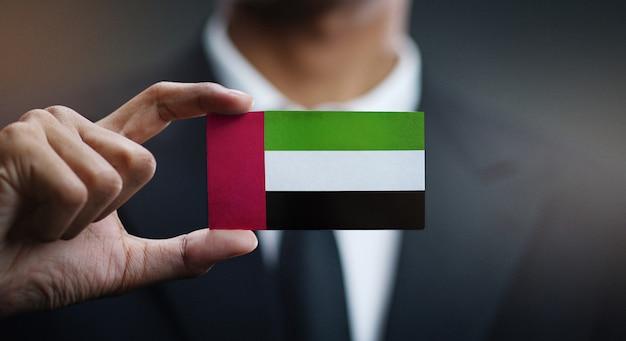Uomo d'affari holding card della bandiera degli emirati arabi uniti
