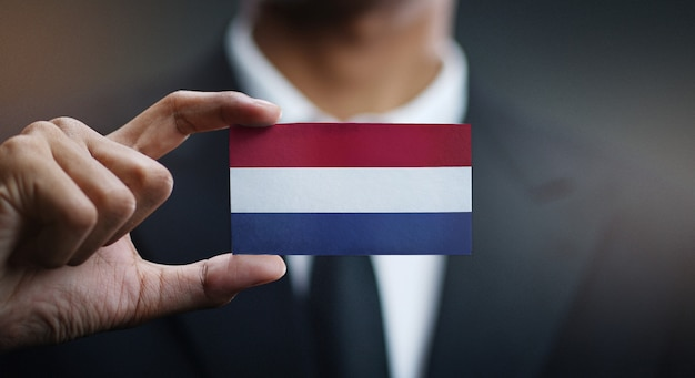 Uomo d'affari holding card della bandiera dei paesi bassi
