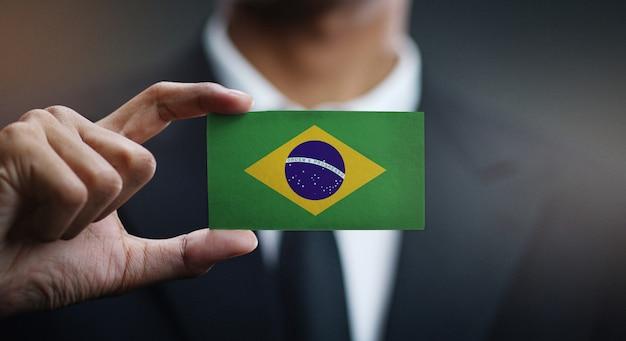 Uomo d'affari holding card della bandiera del brasile