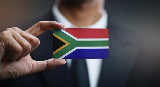 Uomo d'affari holding card della bandiera del sud africa