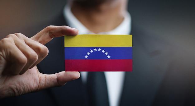Uomo d'affari holding card della bandiera del venezuela