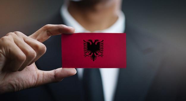 Uomo d'affari holding card della bandiera dell'albania
