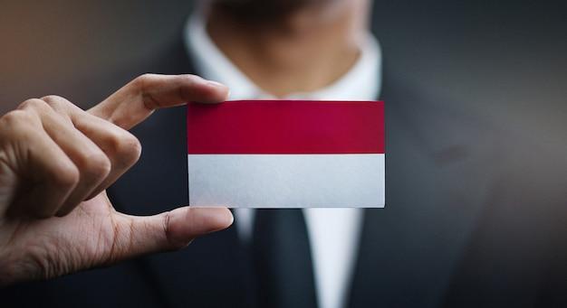 Uomo d'affari holding card della bandiera dell'indonesia