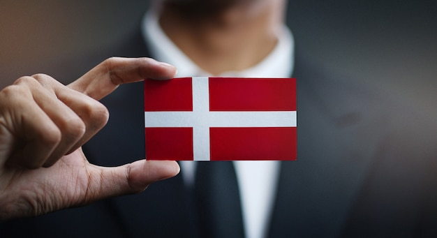 Uomo d'affari holding card della bandiera della danimarca