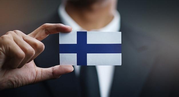 Uomo d'affari holding card della bandiera della finlandia