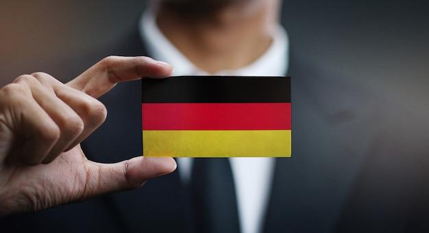 Uomo d'affari holding card della bandiera della germania