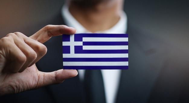 Uomo d'affari holding card della bandiera della grecia