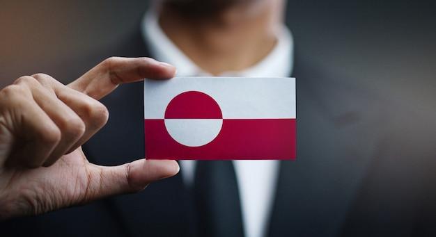 Uomo d'affari holding card della bandiera della groenlandia