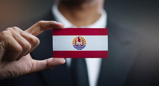 Uomo d'affari holding card della bandiera della polinesia francese
