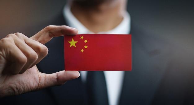 Uomo d'affari holding card of china flag