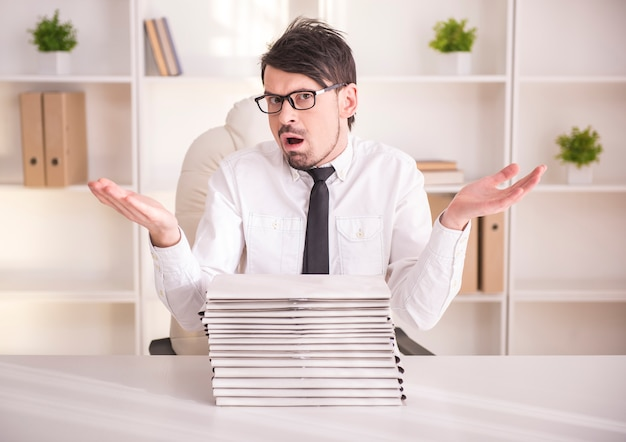Uomo d'affari impegnato con gli occhiali con un sacco di cartelle