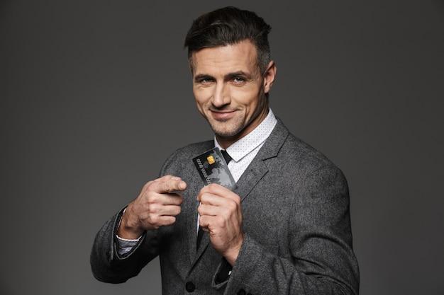 Uomo d'affari in abbigliamento formale che dimostra denaro digitale in carta di credito in plastica, isolato sopra il muro grigio