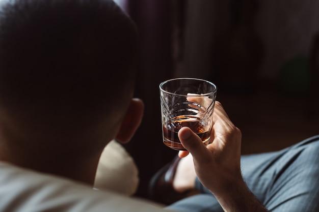 Uomo d'affari in abito elegante con un bicchiere di whisky