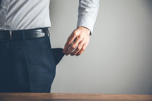 Uomo d'affari in bancarotta mostrando mano tasca vuota