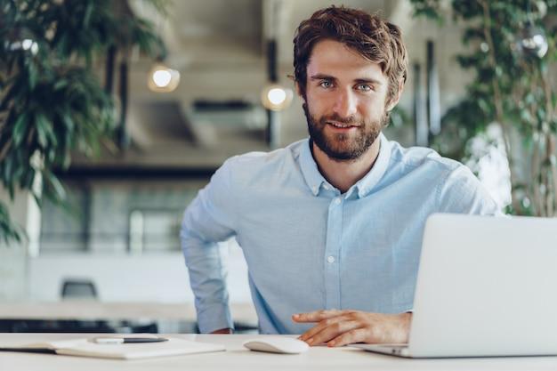 Uomo d'affari in camicia che lavora al suo computer portatile in un ufficio. ufficio open space
