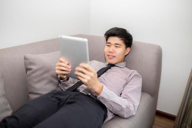 Uomo d'affari in camicia formale giocando tablet computer, guarda nuovi film, utilizzando la connessione internet gratuita, gode di conversazione con gli amici nei social network e sdraiato sul safa a casa.