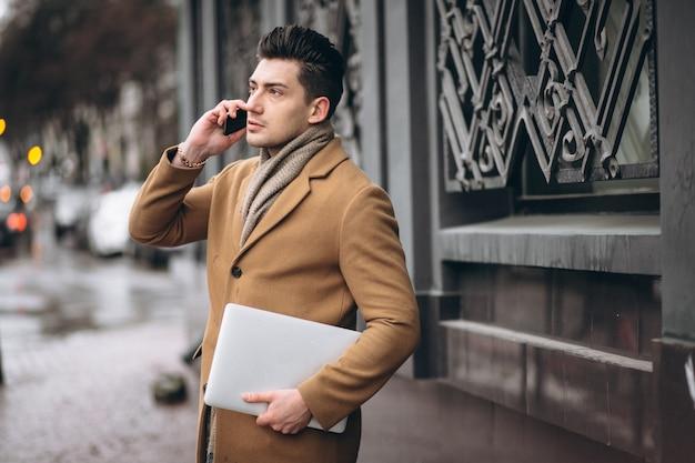 Uomo d'affari in cappotto con il portatile fuori