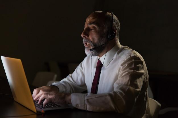 Uomo d'affari in cuffia avricolare che parla e che utilizza computer portatile