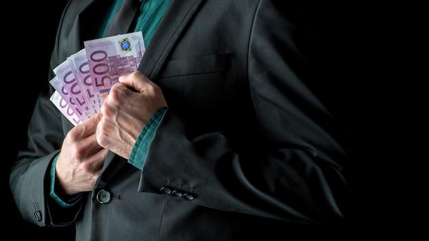 Uomo d'affari in giacca e cravatta in possesso di banconote da 500 euro vicino alla tasca interna della giacca