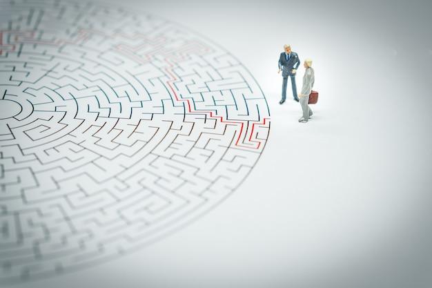 Uomo d'affari in miniatura camminando in un labirinto.