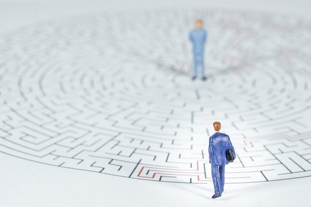 Uomo d'affari in miniatura camminare in un labirinto.